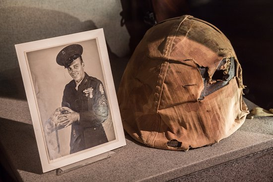 Fredericksburg, TX: A Marine's helmet that took a sniper round. The Marine can be seen holding the helmet.