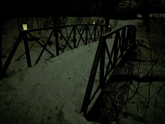 Dundas, MN: Walking bridge over Falls creek, lit by candles