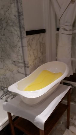 Claridgeu0027s: A Baby Bath Tub And Stand In The Bathroom.