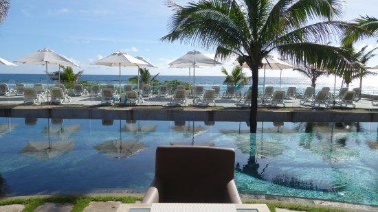 Salle de restauration ouverte sur la piscine et l'océan
