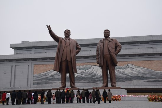 Mansudae Grand Monument: People bowing to the statues and placing flowers.