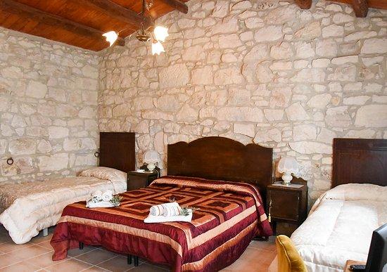 Camera da letto con mura in pietra a secco soffitto in legno e