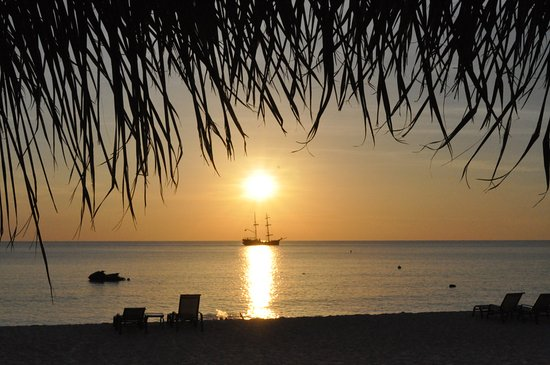 Beachcomber Grand Cayman: Enjoy our sunsets underneath the tiki hut