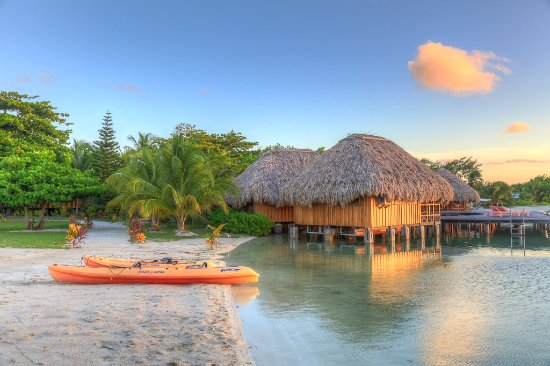 St. George's Caye, Belize: Swimming beach at sunset with kayaks and Overwater Cabanas in background