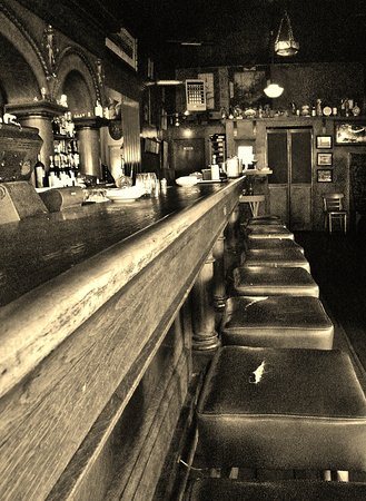The long old wooden bar, seats and surrounding decor - Picture of ...