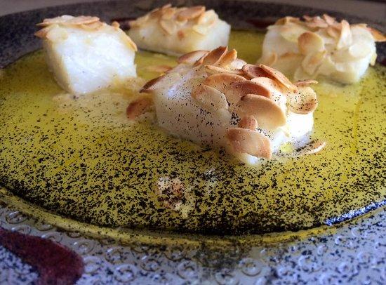 Baccalà gratinato con filetti di mandorla, salsa all'arancia e polvere di nero di seppia