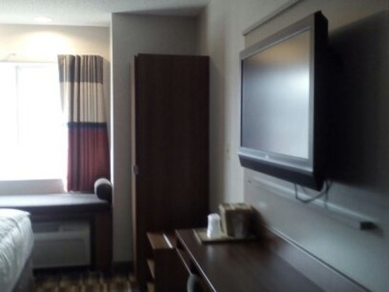 Microtel Inn & Suites by Wyndham Philadelphia Airport: room with double bed, closet, computer table and sitting area.