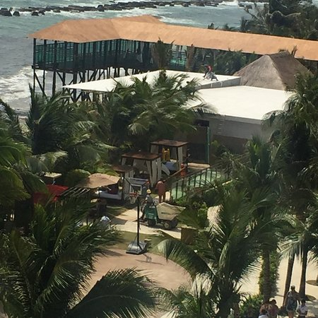 Construction work near pool and cabanas and seaweed farm equipment tractors going up and down be