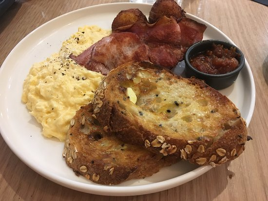 Balgowlah, Australia: Scrambled eggs with potato hash, double bacon, onion jam and seeded soughdough toast