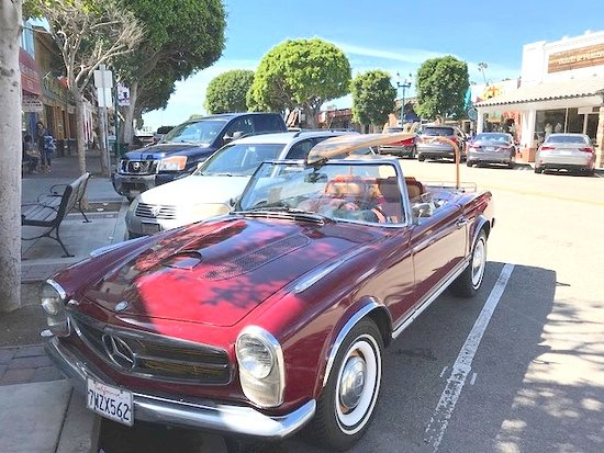 Seal Beach, CA: cute car with surf board parked in shopping area