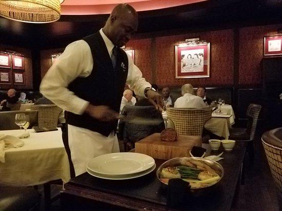 BR Prime Steakhouse: Waiter slicing our steak at tableside.