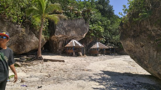 Higatangan Island, Filippinerna: Shaded huts on the resort beach