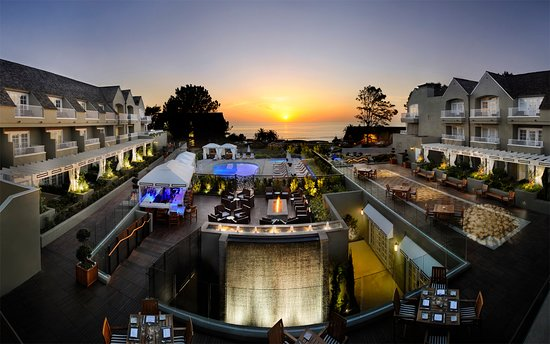 View of a sunset over L'Auberge Del Mar's Coastline restaurant and swimming pool