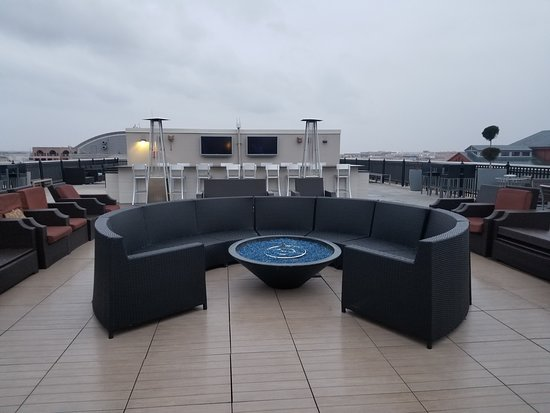 Capital View: Rooftop lounge area with grills, tvs, tables, seating, and firepits.