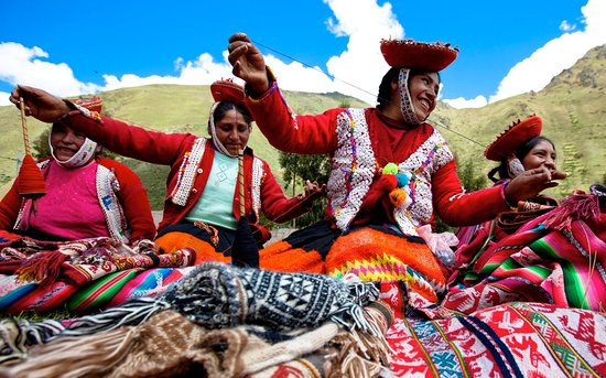 Ollantaytambo, Perú: Our partner artisans wear the bright colors of traditional Quechua dress as they spin and weave.