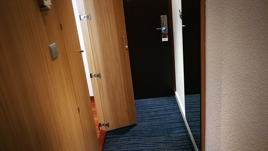 Narrow passage leading from front door past small bathroom.