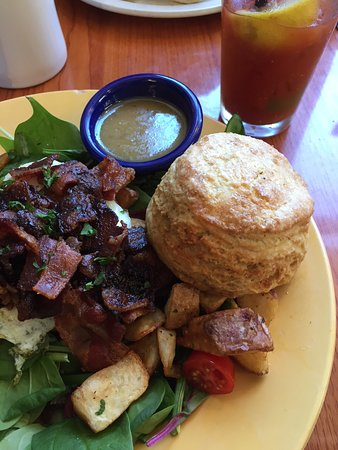 Breakfast salad with bacon and a biscuit.