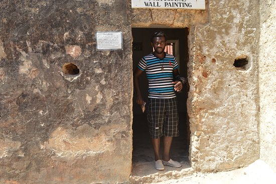 Fort Jesus Museum: me standing right in the door way to the wall paintings that have lasted over 200 years