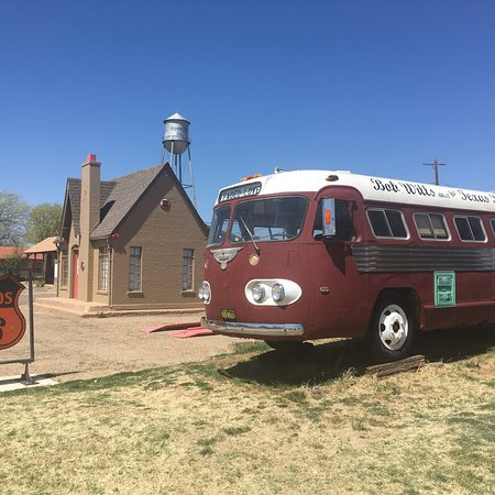 Turkey, TX: The Texas Playboys tour bus parked next to a restored Phillips 66 station.