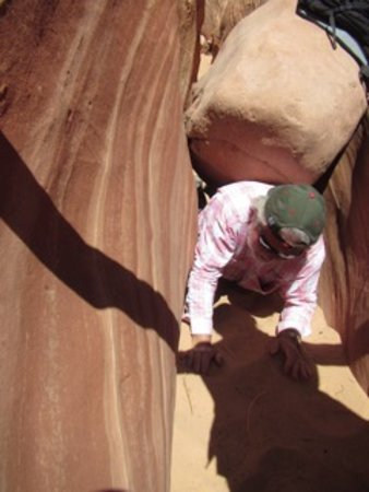 Desert DAWN: Crawling under a Boulder in a slot canyon