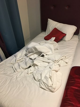 The Belvedere Hotel: Unmade bed with dirty towels left behind