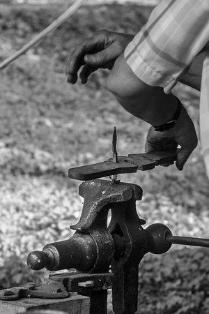 Belvidere, TN: A craftsmans hands working at the Blacksmith shop.