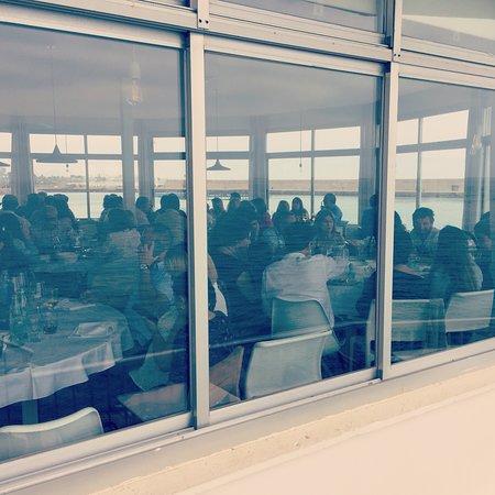 Burriana, España: vista del restaurante con el reflejo del mar en las ventanas