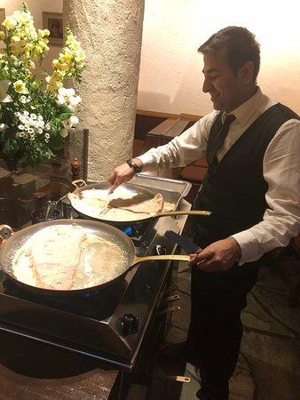 Walliser Kanne: Staff preparing schnitzel in the dining area.