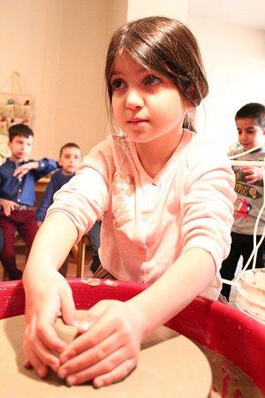 In Art Studio: kids trying pottery