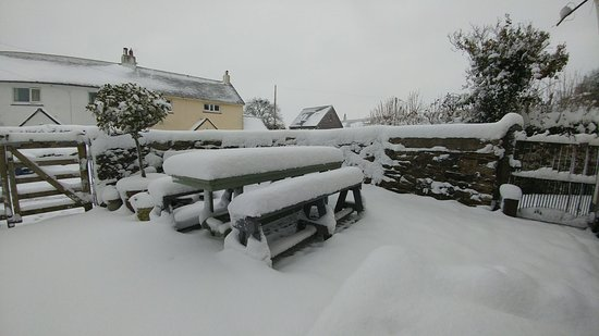 Ilsington, UK: When it snow it certainly snows. My pint is on that table somewhere.