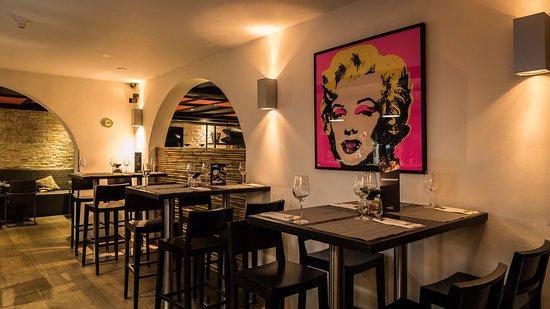 Hoge tafels tegenover de bar bij Restaurant WEI
