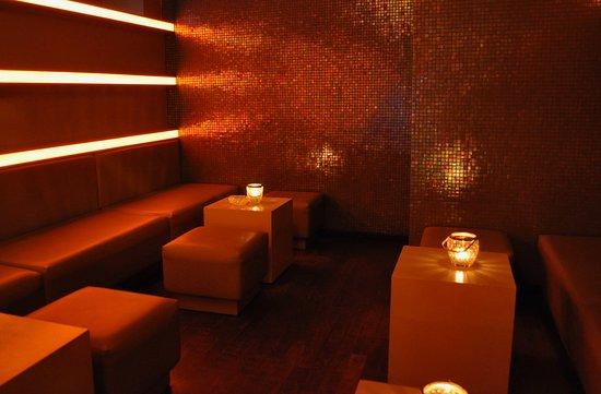 Perle Bar: Sanft schimmerndes Licht vor der irisierenden Mosaikfliesenwand.