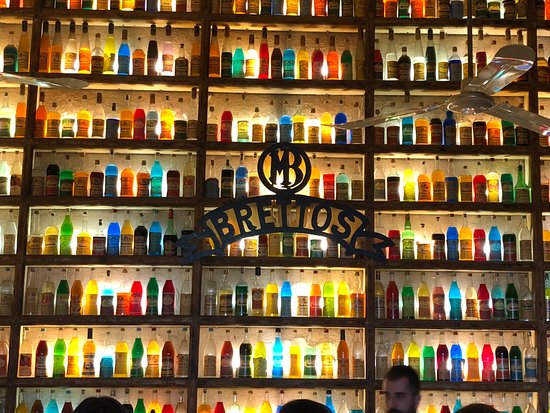 Brettos Bar: Backdrop of the wall with all the colorful bottles of ouzo.