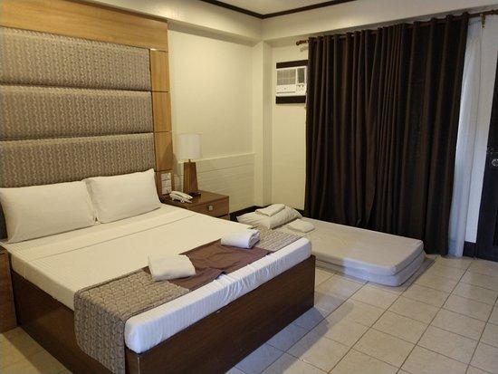 """โรงแรมอีออน เซ็นเท็นเนียล พลาซ่า: Floor on the bed in an """"Executive Room"""". Ancient A/C unit in room."""