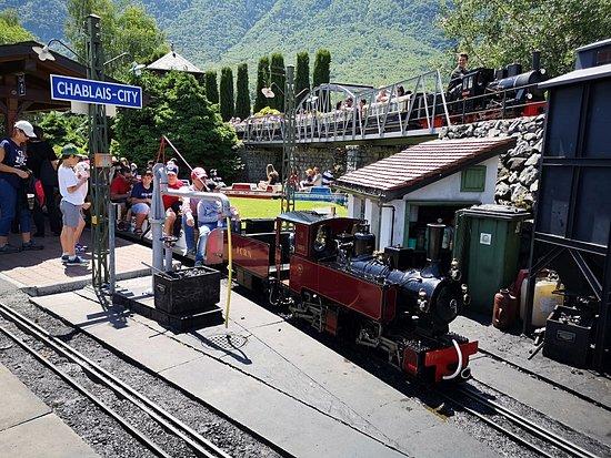 Swiss Vapeur Parc: A toute vapeur ! Un train en gare et un autre qui passe sur le circuit du haut !