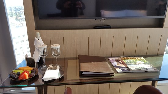 Sofitel Sydney Darling Harbour: TV and desk with welcome drink