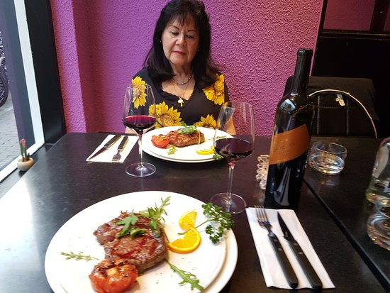 Carne Argentina: Mijn vrouw kijkt verheeerlijkt naar het versierde bord met de rib eye en gepofte tomaat