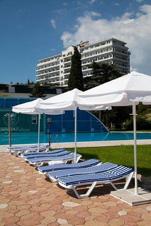 Riviera Sunrise Resort & Spa Alushta: Шезлонги и зонты на фоне собственного подогреваемого бассейна с баром и корпуса Modern
