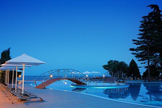 Riviera Sunrise Resort & Spa Alushta: Собственный открытый бассейн на фоне моря в вечернее время