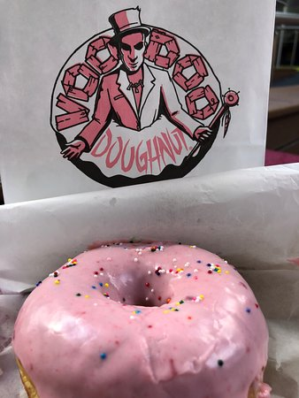 Little pink raised doughnut with strawberry icing and