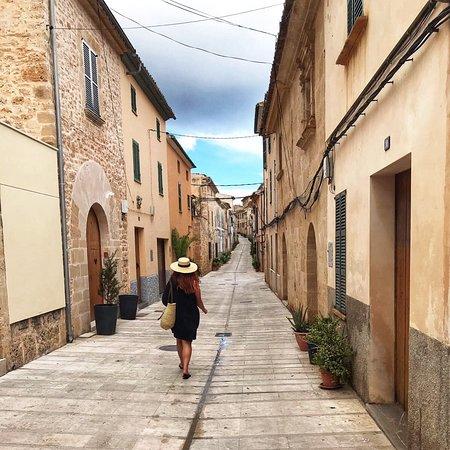 woman in black dress and straw hat walking down a quiet Italian street