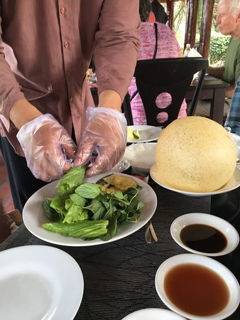 Ben Tre Province, Vietnam: Waiter preparing spring rolls at our table from fish and greens