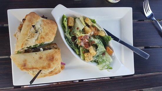 Symposium Cafe Restaurant and Lounge: Pesto chicken sandwich with Caesar salad