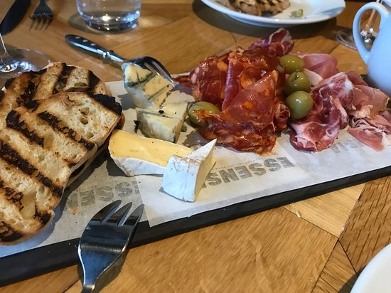Platter of mixed sliced Italian parma ham, cold cuts and cheeses. Grilled bread, olives