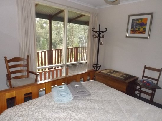 Main bedroom in Ruby Cottage, with view out of window to Wirrabara Forest