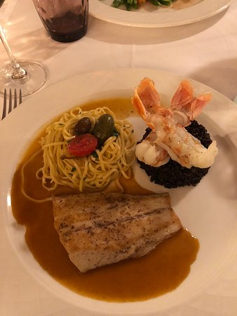 Fish in lobster reduction with tagliatelle, garnish of black rice with shrimp