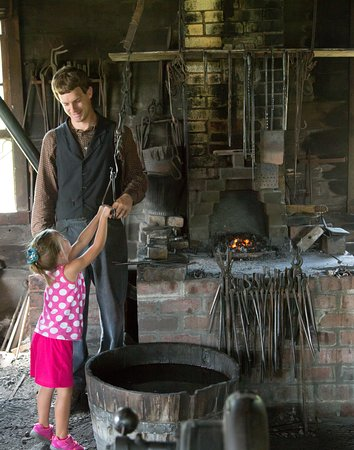 Living History Farms: A visitor helps operate the bellows in the 1875 era blacksmith shop.
