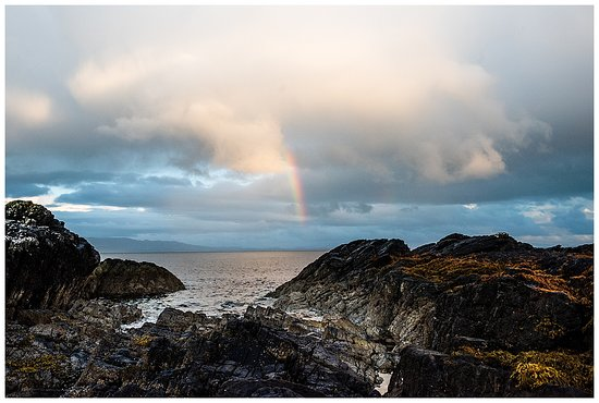 Ardvasar, UK: Rainbow over the water and the rocky shoreline just beyond the meadow