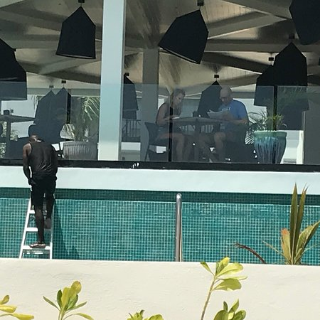 Excellence Oyster Bay: Doing maintenance around the pool area while people swimming. Scrapings going into the water ...