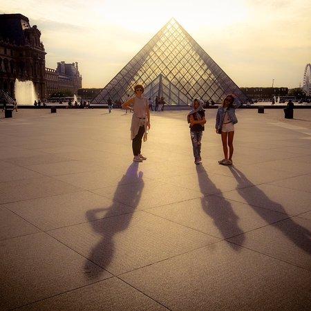 Лувр: Vista exterior de la piramide de cristal al anochecer.